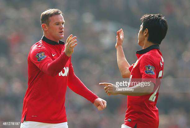 Wayne Rooney of Manchester United celebrates scoring his team's first goal with Shinji Kagawa during the Barclays Premier League match between...