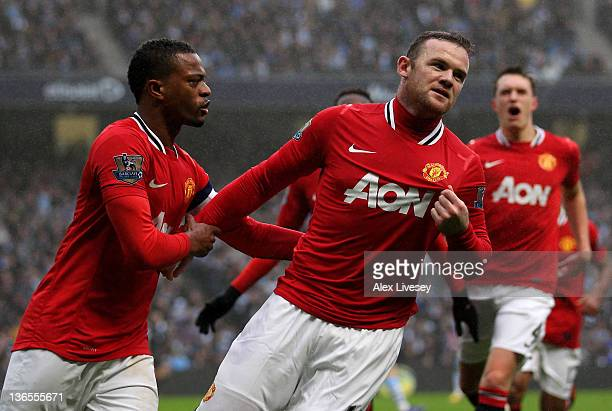 Wayne Rooney of Manchester United celebrates scoring the opening goal with Patrice Evra during the FA Cup Third Round match between Manchester City...