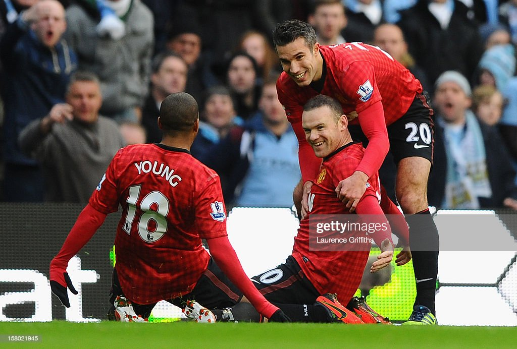 Wayne Rooney of Manchester United celebrates scoring the opening goal with team-mates Ashley Young and Robin van Persie (R) during the Barclays Premier League match between Manchester City and Manchester United at the Etihad Stadium on December 9, 2012 in Manchester, England.