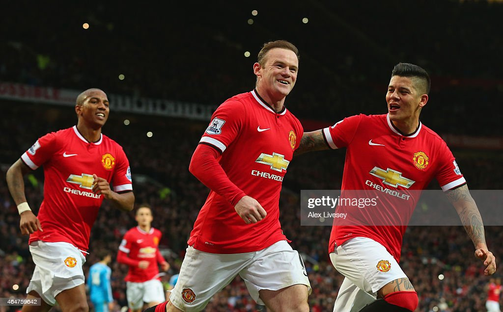 Wayne Rooney of Manchester United celebrates scoring the opening goal with Marcos Rojo and Ashley Young of Manchester United during the Barclays Premier League match between Manchester United and Sunderland at Old Trafford on February 28, 2015 in Manchester, England.