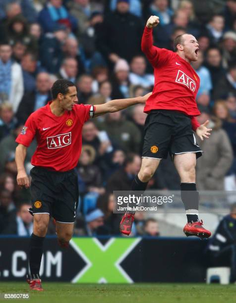Wayne Rooney of Manchester United celebrates scoring the opening goal with team mate Rio Ferdinand during the Barclays Premier League match between...