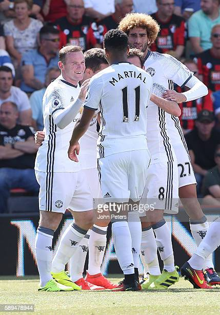 Wayne Rooney of Manchester United celebrates scoring the second goal to make the score 02 with his teammates during the Premier League match between...