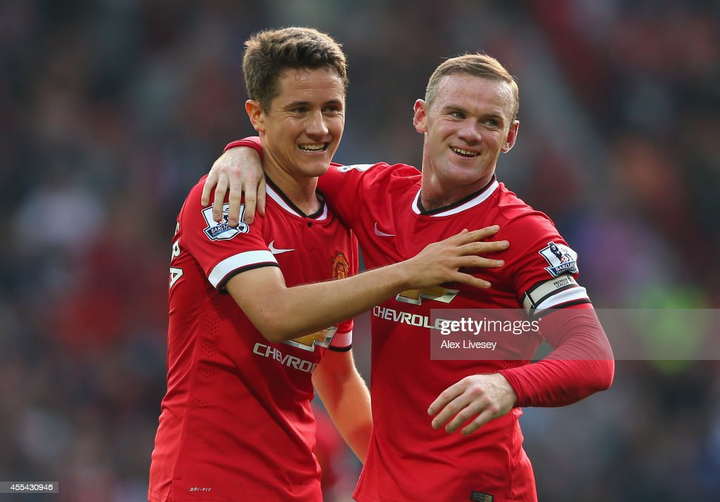 Wayne Rooney of Manchester United celebrates scoring the third goal with team-mate Ander Herrera (L), during the Barclays Premier League match between Manchester United and Queens Park Rangers at Old Trafford on September 14, 2014 in Manchester, England.