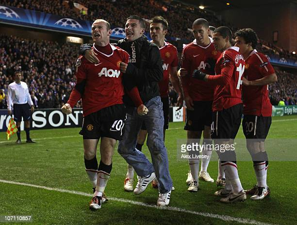 Wayne Rooney of Manchester United celebrates with a supporter after scoring the winning goal from the penalty spot during the UEFA Champions League...