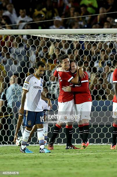 Wayne Rooney of Manchester United celebrates with Ander Herrera after making a penalty kick as Juninho of the Los Angeles Galaxy reacts in the first...
