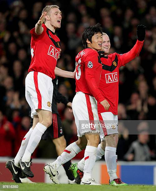Wayne Rooney of Manchester United celebrates with team mates Darren Fletcher and Ji-Sung Park after scoring his team's second goal during the UEFA...