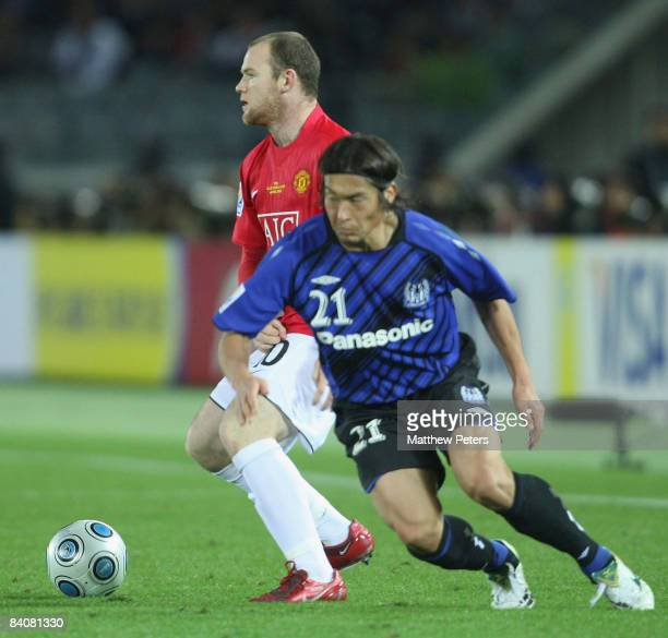 Wayne Rooney of Manchester United clashes with Akira Kaji of Gamba Osaka during the FIFA World Club Cup SemiFinal match between Gamba Osaka and...