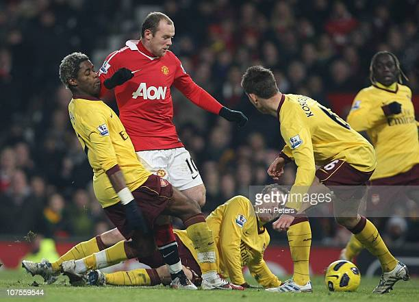 Wayne Rooney of Manchester United clashes with Alex Song Sebastien Squillaci and Laurent Koscielny of Arsenal during the Barclays Premier League...
