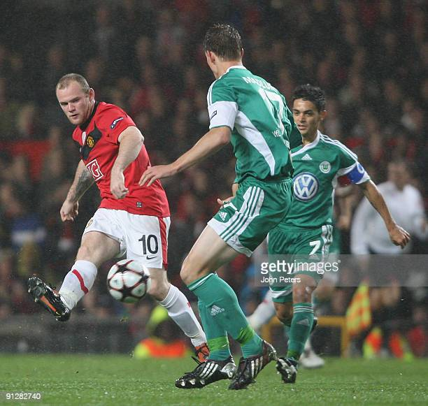 Wayne Rooney of Manchester United clashes with Alexander Madlung of Wolfsburg during the UEFA Champions League match between Manchester United and...