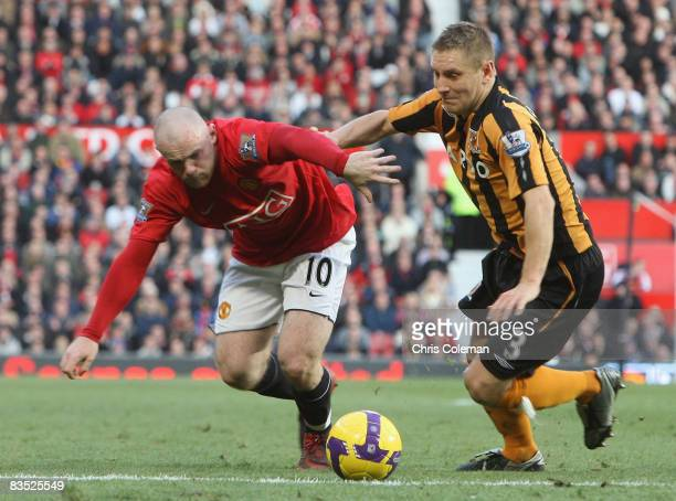 Wayne Rooney of Manchester United clashes with Andy Dawson of Hull City during the Barclays Premier League match between Manchester United and Hull...