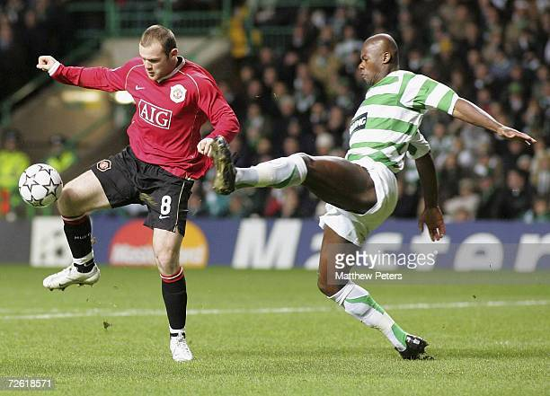 Wayne Rooney of Manchester United clashes with Bobo Balde of Celtic during the UEFA Champions League match between Celtic and Manchester United at...