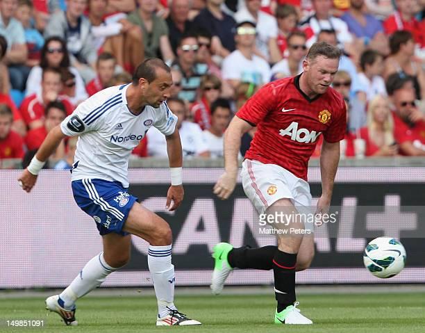 Wayne Rooney of Manchester United clashes with Bojan Zajic of Valerenga FC during the preseason match between Valerenga FC and Manchester United at...