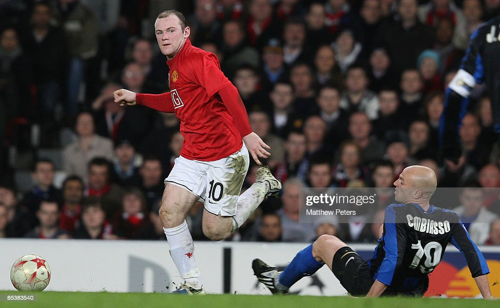 Wayne Rooney of Manchester United clashes with Esteban Cambiasso of Inter Milan during the UEFA Champions League First Knockout Round Second Leg match between Manchester United and Inter Milan at Old Trafford on March 11 2009, in Manchester, England.