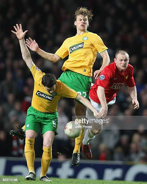 Wayne Rooney of Manchester United clashes with Gary Caldwell and Glenn Loovens of Celtic during the UEFA Champions League Group E match between...