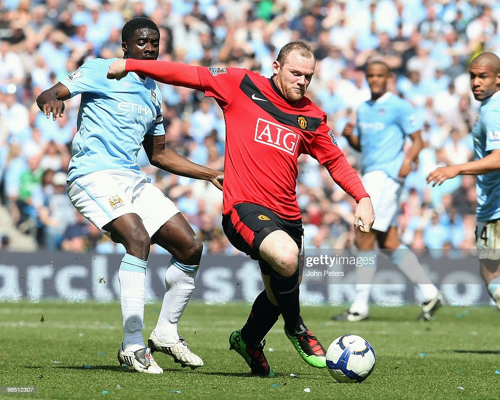 Wayne Rooney of Manchester United clashes with Kolo Toure of Manchester City during the Barclays Premier League match between Manchester City and Manchester United at City of Manchester Stadium on April 17 2010 in Manchester, England.