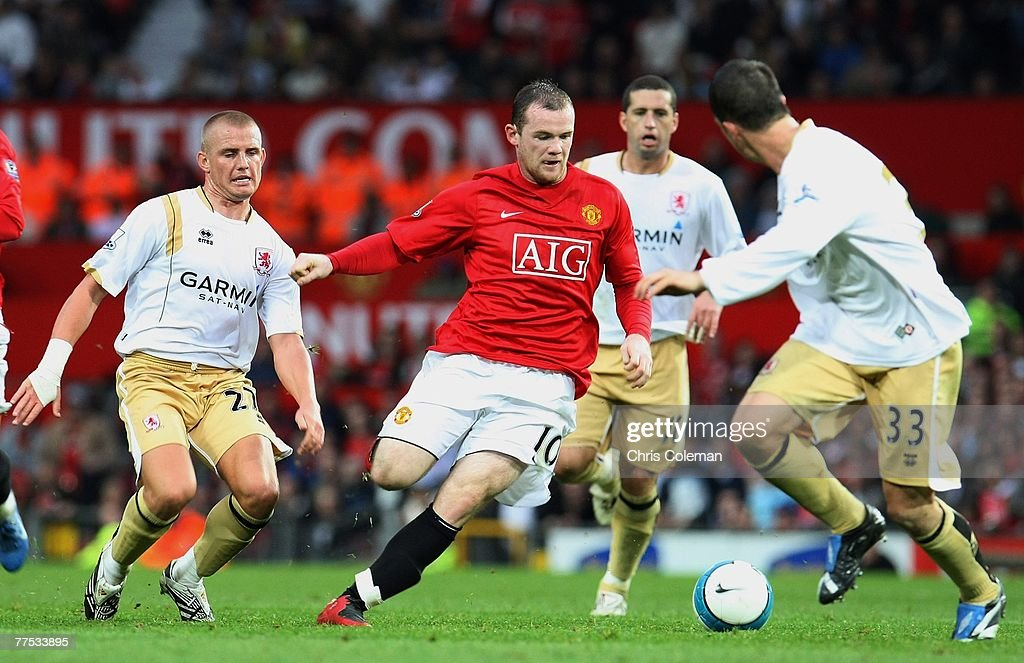 Wayne Rooney of Manchester United clashes with Lee Cattermole and Andrew Taylor of Middlesbrough during the Barclays FA Premier League match between Manchester United and Middlesbrough at Old Trafford on October 27 2007 in Manchester, England.