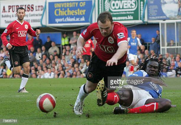 Wayne Rooney of Manchester United clashes with Linvoy Primus of Portsmouth during the Barclays Premiership match between Portsmouth and Manchester...