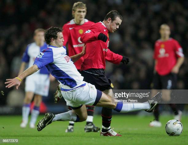 Wayne Rooney of Manchester United clashes with Lucas Neill of Blackburn Rovers during the Carling Cup semifinal first leg match between Blackburn...