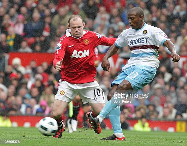 Wayne Rooney of Manchester United clashes with Luis Boa Morte of West Ham United during the Barclays Premier League match between Manchester United...