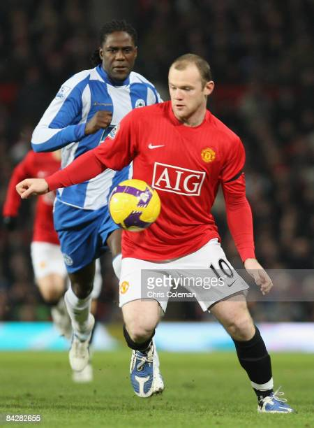 Wayne Rooney of Manchester United clashes with Mario Melchiot of Wigan Athletic during the Barclays Premier League match between Manchester United...