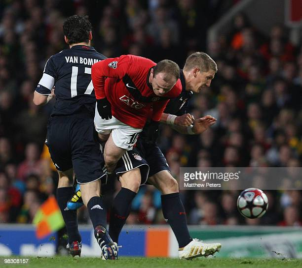 Wayne Rooney of Manchester United clashes with Mark van Bommel and Bastian Schweinsteiger of Bayern Munich during the UEFA Champions League...