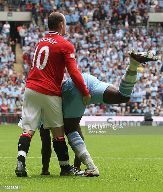 Wayne Rooney of Manchester United clashes with Micah Richards of Manchester City during the FA Community Shield match between Manchester City and...