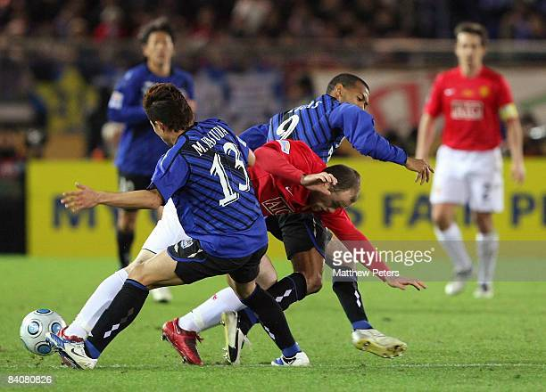 Wayne Rooney of Manchester United clashes with Michihiro Yasuda and Lucas of Gamba Osaka during the FIFA World Club Cup Semi-Final match between...