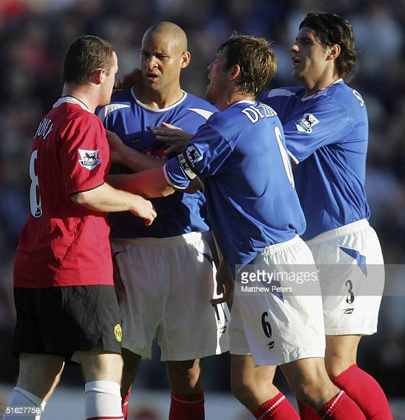 Wayne Rooney of Manchester United clashes with Nigel Quashie, Arjan de Zeeuw and Dejan Stefanovic of Portsmouth during the Barclays Premiership match...