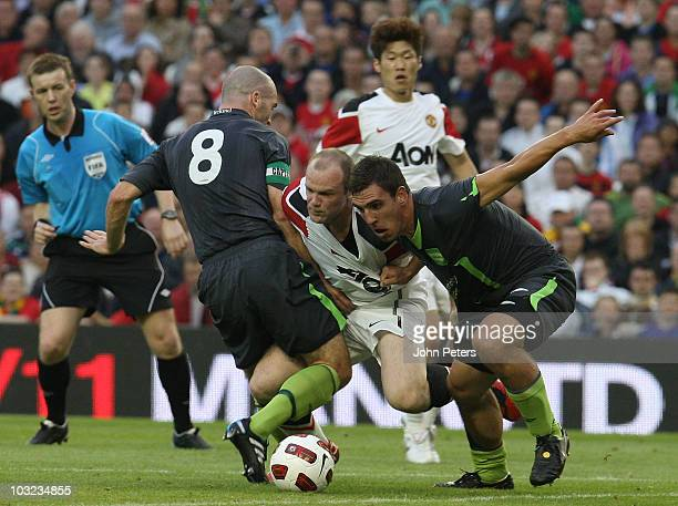 Wayne Rooney of Manchester United clashes with Paul Keegan and Gavin Peers of the Irish League XI during the preseason friendly match between Irish...