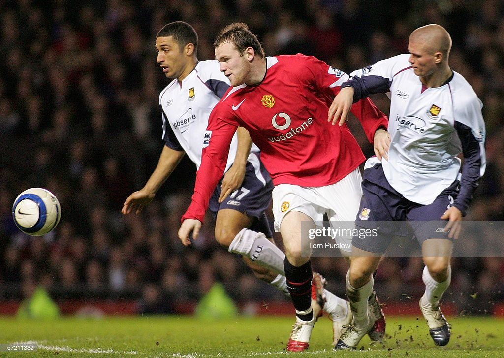 Wayne Rooney of Manchester United clashes with Paul Konchesky and Hayden Mullins of West Ham United during the Barclays Premiership match between Manchester United and West Ham United at Old Trafford on March 29 2006 in Manchester, England.