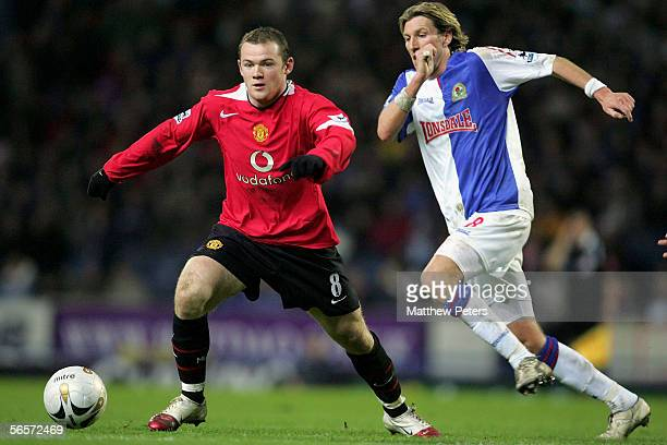Wayne Rooney of Manchester United clashes with Robbie Savage of Blackburn Rovers during the Carling Cup semifinal first leg match between Blackburn...