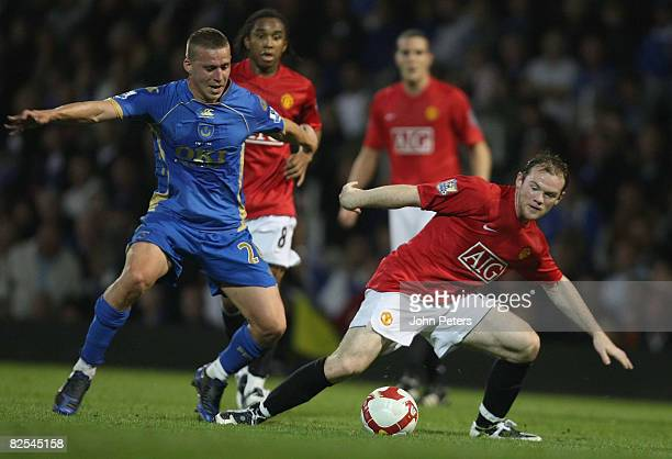 Wayne Rooney of Manchester United clashes with Sean Davis of Portsmouth during the FA Premier League match between Portsmouth and Manchester United...