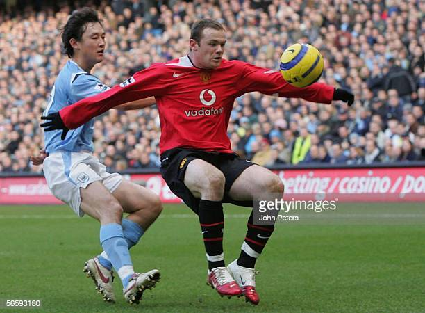 Wayne Rooney of Manchester United clashes with Sun Jihai of Manchester City during the Barclays Premiership match between Manchester City and...