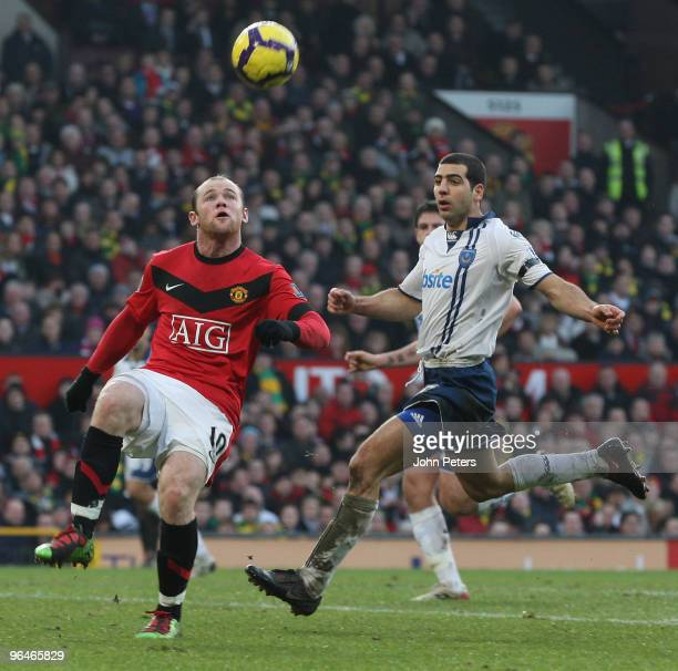 Wayne Rooney of Manchester United clashes with Tal Ben Haim of Portsmouth during the FA Barclays Premier League match between Manchester United and...
