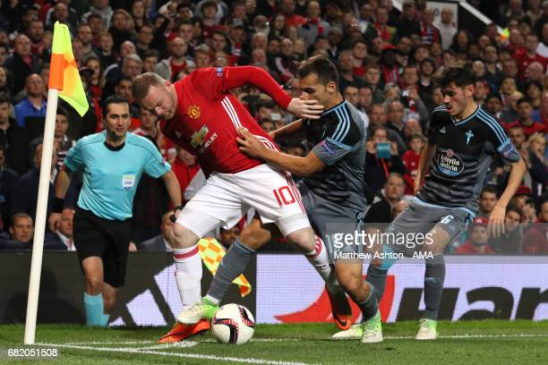 Wayne Rooney of Manchester United competes with Jonny of Celta Vigo during the UEFA Europa League semi final second leg match between Manchester...
