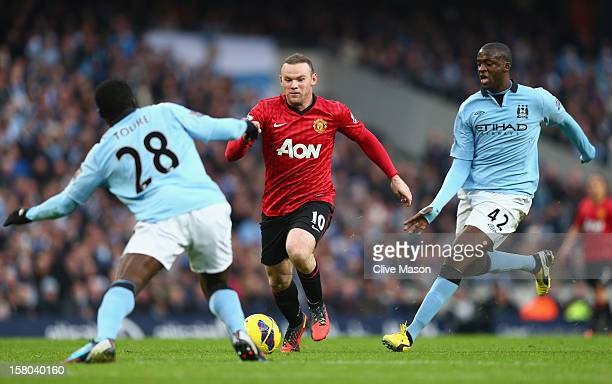 Wayne Rooney of Manchester United competes with Kolo Toure and Yaya Toure of Manchester City in action during the Barclays Premier League match...