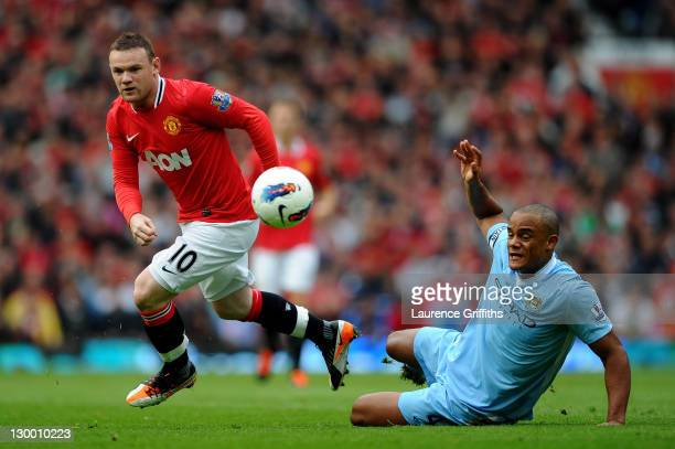 Wayne Rooney of Manchester United competes with Vincent Kompany of Manchester City during the Barclays Premier League match between Manchester United...