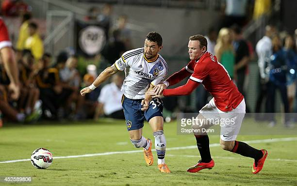 Wayne Rooney of Manchester United fights for the ball with Dan Gargan of the Los Angeles Galaxy at the Rose Bowl on July 23 2014 in Pasadena...