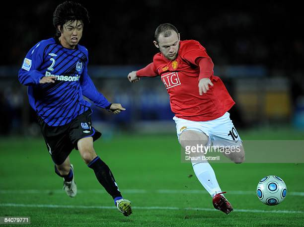 Wayne Rooney of Manchester United fires in his first goal as Sota Nakazawa of Gamba Osaka looks on during the FIFA Club World Cup Japan 2008 Semi...