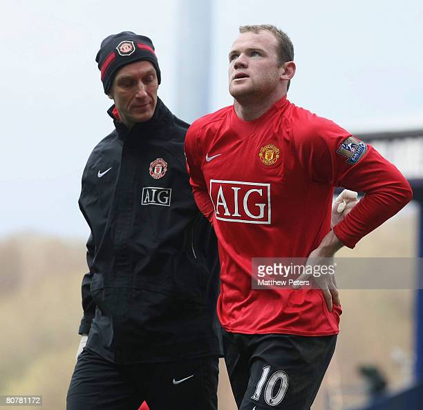 Wayne Rooney of Manchester United holds his side after picking up an injury during the Barclays FA Premier League match between Blackburn Rovers and...