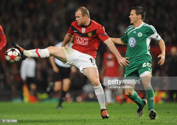Wayne Rooney of Manchester United holds off the challenge of Sascha Riether of VfL Wolfsburg during the UEFA Champions League Group B match between...