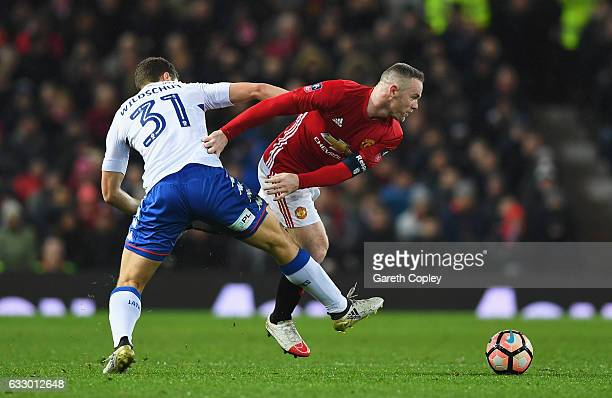 Wayne Rooney of Manchester United holds off Yanic Wildschut of Wigan Athletic during the Emirates FA Cup Fourth round match between Manchester United...