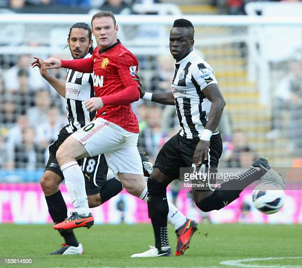 Wayne Rooney of Manchester United in action against Jonas Gutierrez and Chiek Tiote of Newcastle United during the Barclays Premier League match...