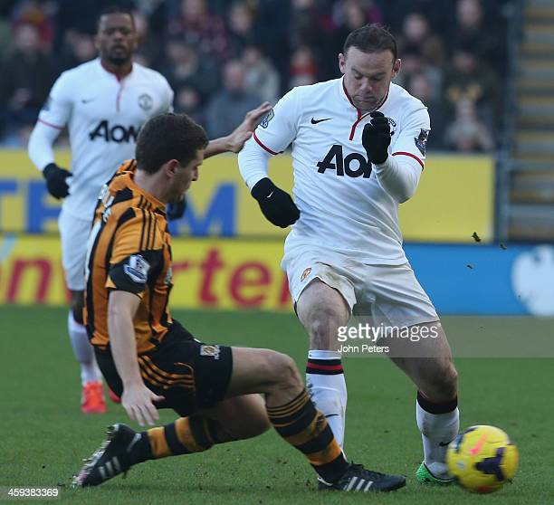 Wayne Rooney of Manchester United in action with Alex Bruce of Hull City during the Barclays Premier League match between Hull City and Manchester...