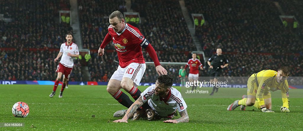 Wayne Rooney of Manchester United in action with David Edgar and George Long of Sheffield United during the Emirates FA Cup Third Round match between Manchester United and Sheffield United at Old Trafford on January 9, 2016 in Manchester, England.