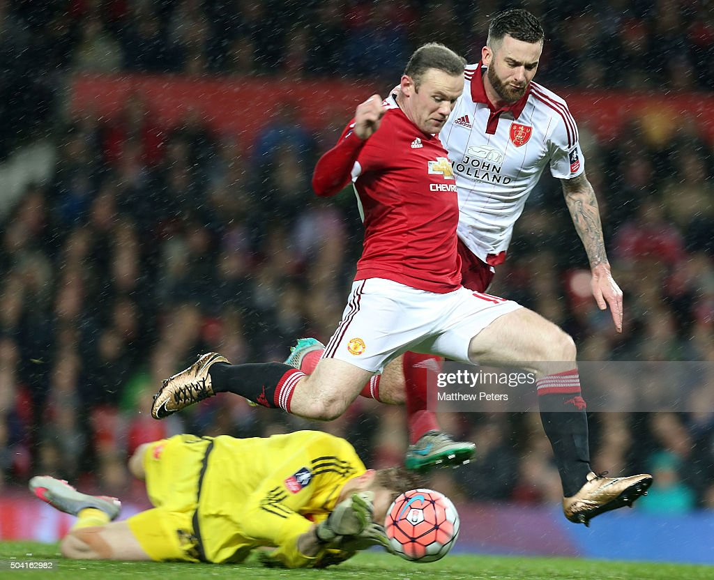 Wayne Rooney of Manchester United in action with George Long and David Edgar of Sheffield United during the Emirates FA Cup Third round match between Manchester United and Sheffield United at Old Trafford on January 9, 2016 in Manchester, England.