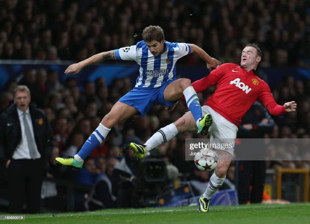 Wayne Rooney of Manchester United in action with Inigo Martinez of Real Sociedad during the UEFA Champions League Group A match between Manchester United and Real Sociedad at Old Trafford on October 23, 2013 in Manchester, England.