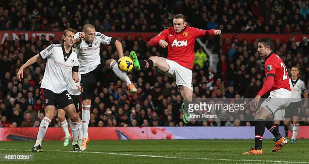 Wayne Rooney of Manchester United in action with John Heitinga of Fulham during the Barclays Premier League match between Manchester United and...