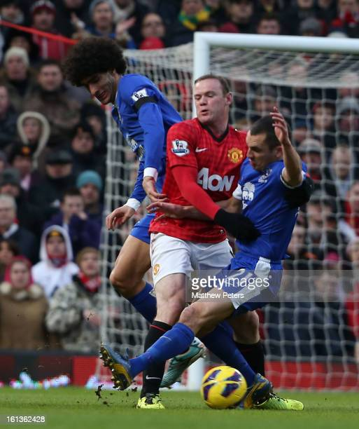 Wayne Rooney of Manchester United in action with Marouane Fellaini and Leon Osman of Everton during the Barclays Premier League match between...