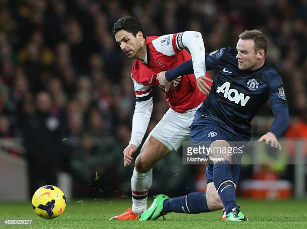 Wayne Rooney of Manchester United in action with Mikel Arteta of Arsenal during the Barclays Premier League match between Arsenal and Manchester...